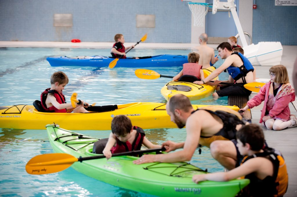 A big group of participants in kayakis in the pool with one on one instructors who are teaching them how to kayak.