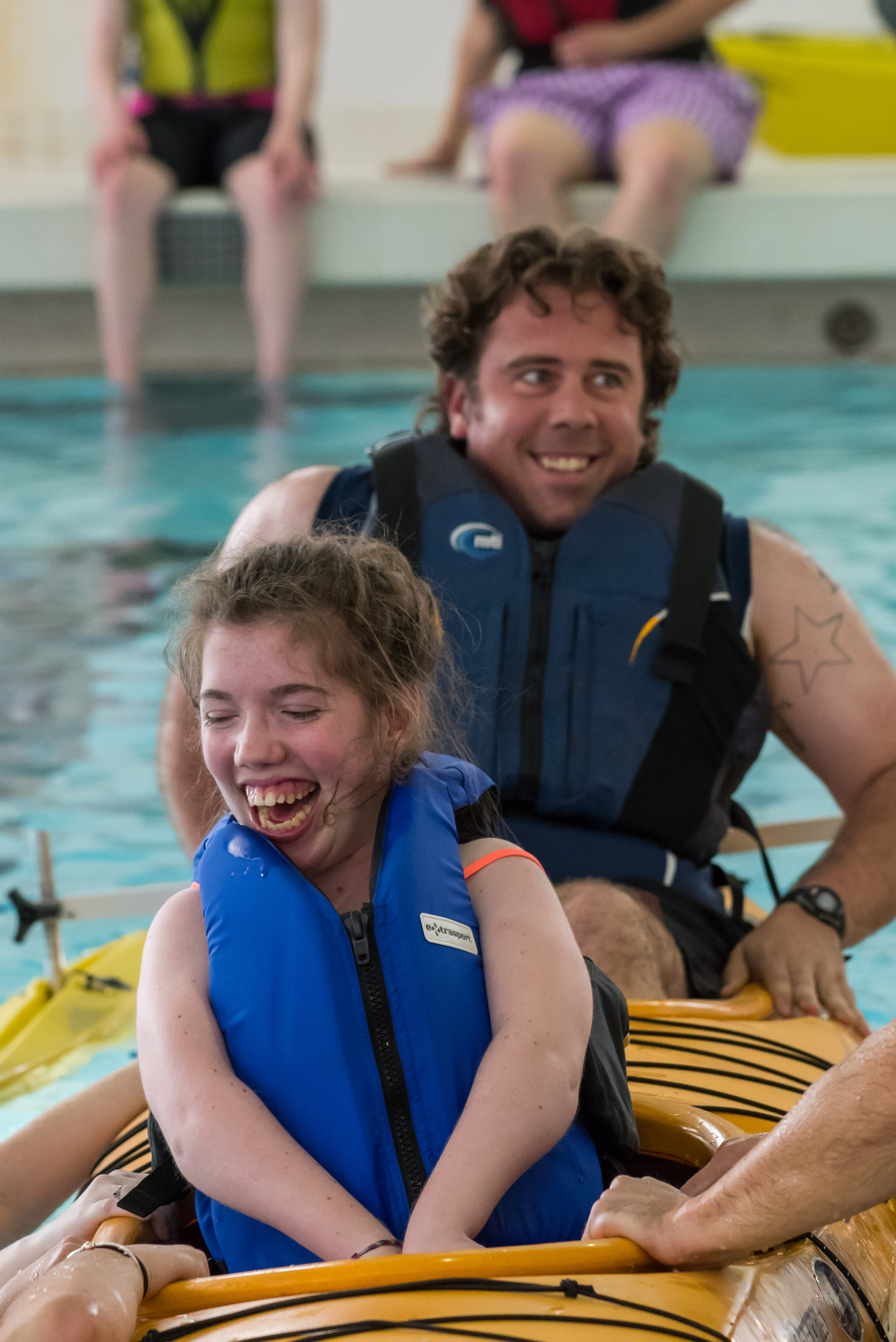 Two people getting into a kayak in a pool. Both are smiling and laughing.
