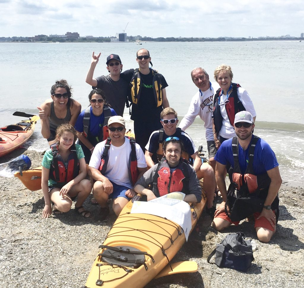 A group of kayaking participants all posing for the camera during a kayak program on the boston harbor. One participant is still in his boat on shore and all of the others are gathered around him.