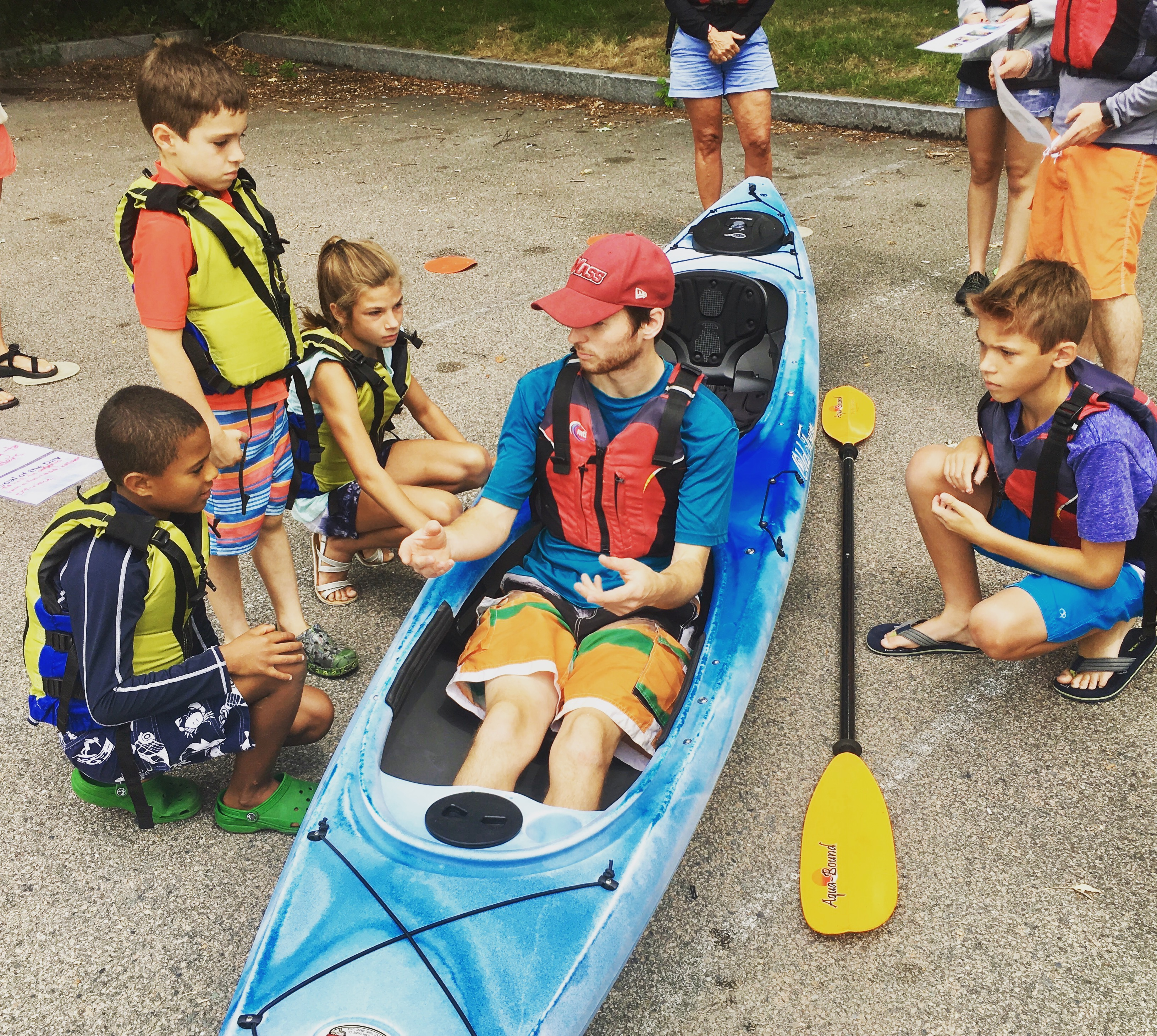 An LIT sitting in a kayak while it sits on the pavement surrounded by children who are learning about where to put your feet