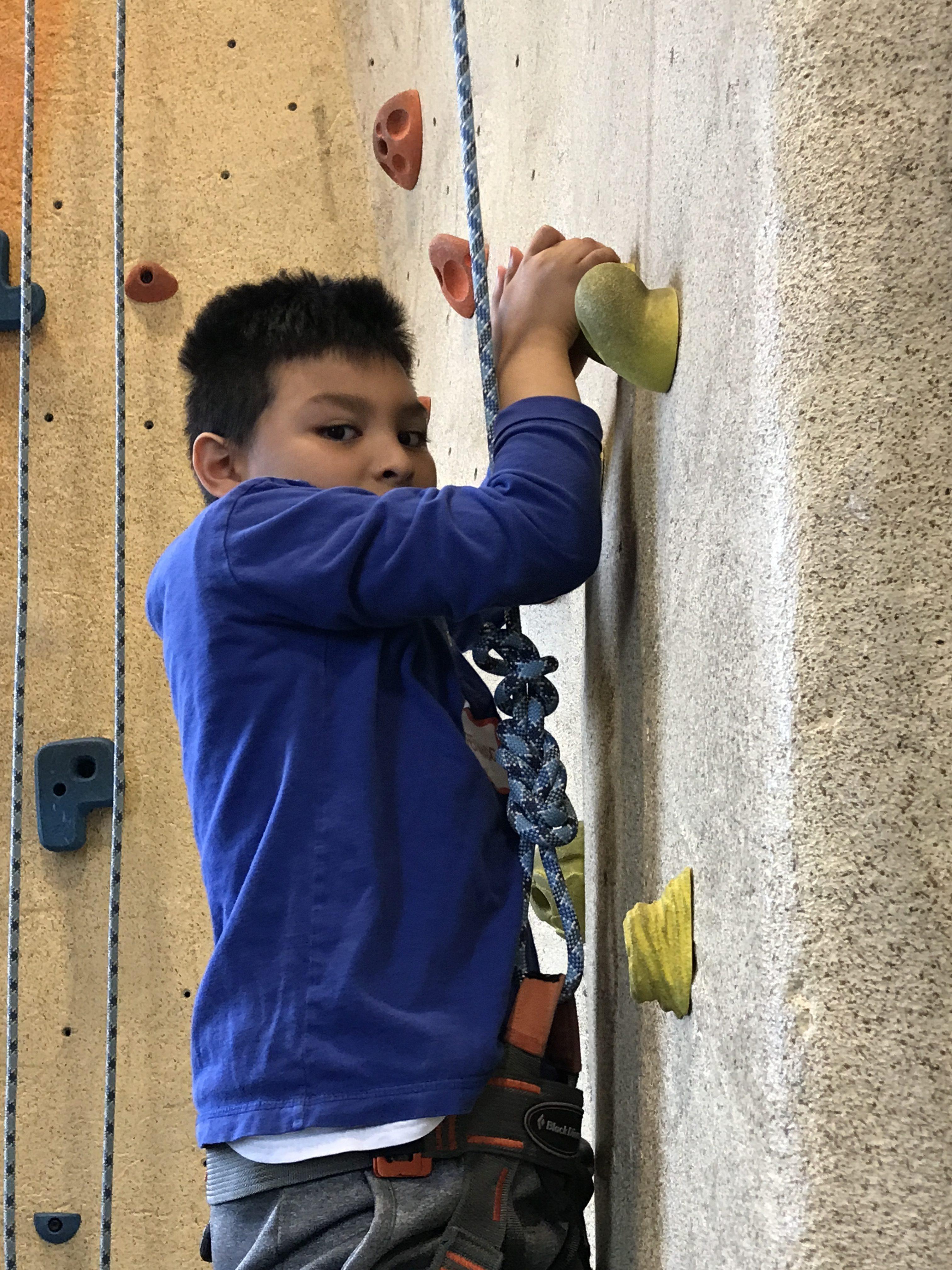 boy indoor rock climbing