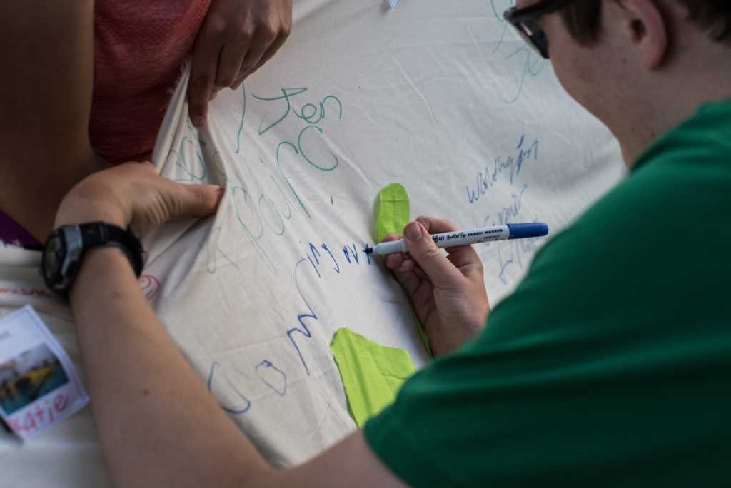 Picture of a participant writing his moment of courage on the Waypoint banner.