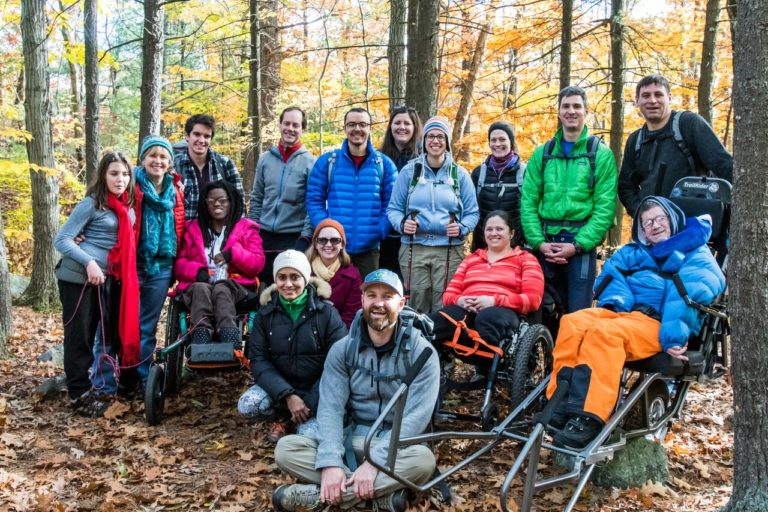 group of people dressed in winter clothing in the woods, some using wheelchairs, some carrying trekking poles, all smiling and happy
