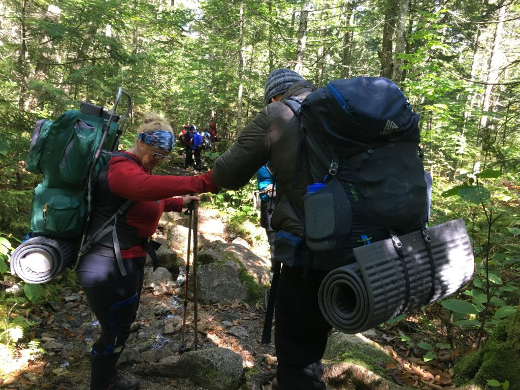People helping participants while hiking