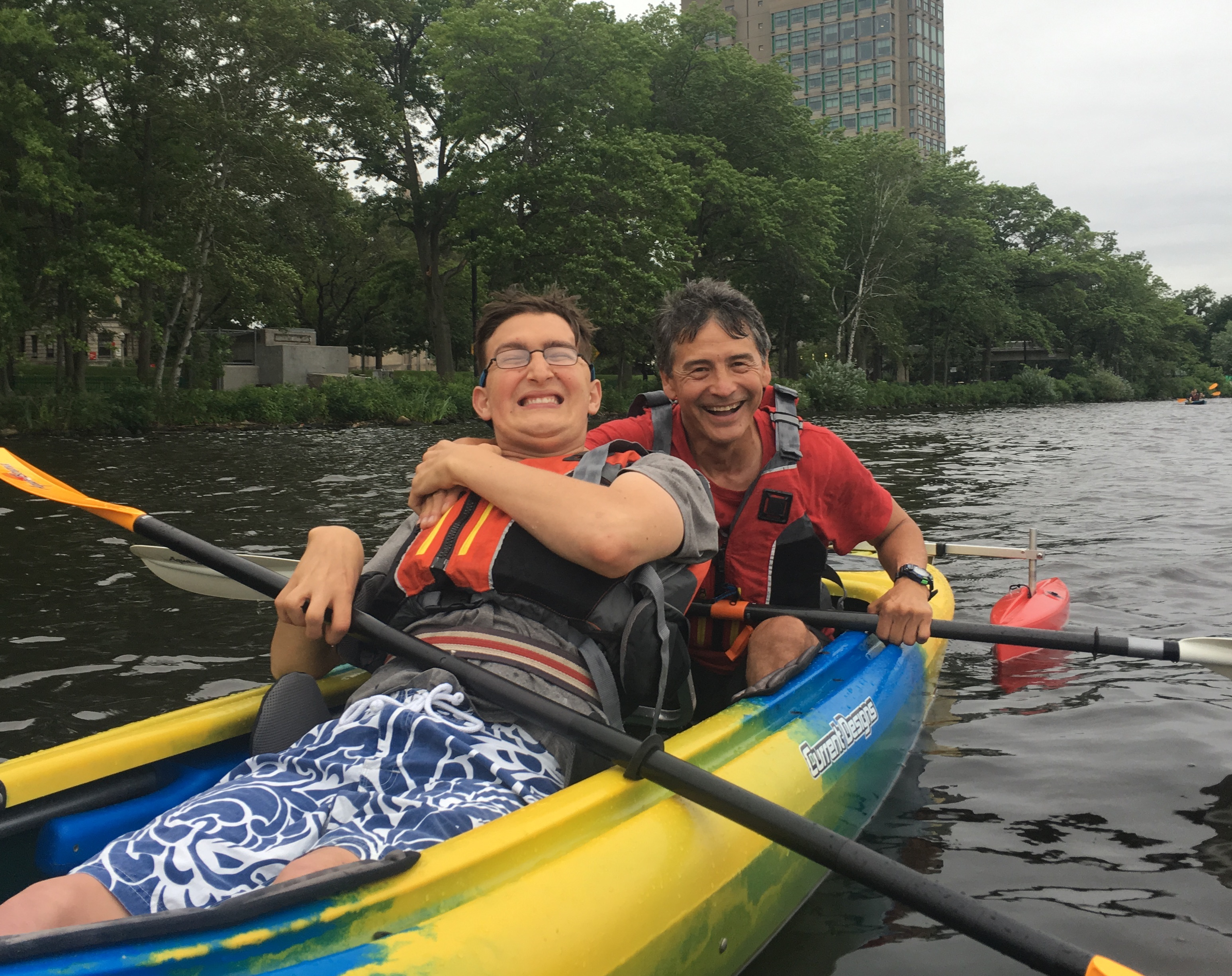 Paddle partners in kayak with large smiles on their faces