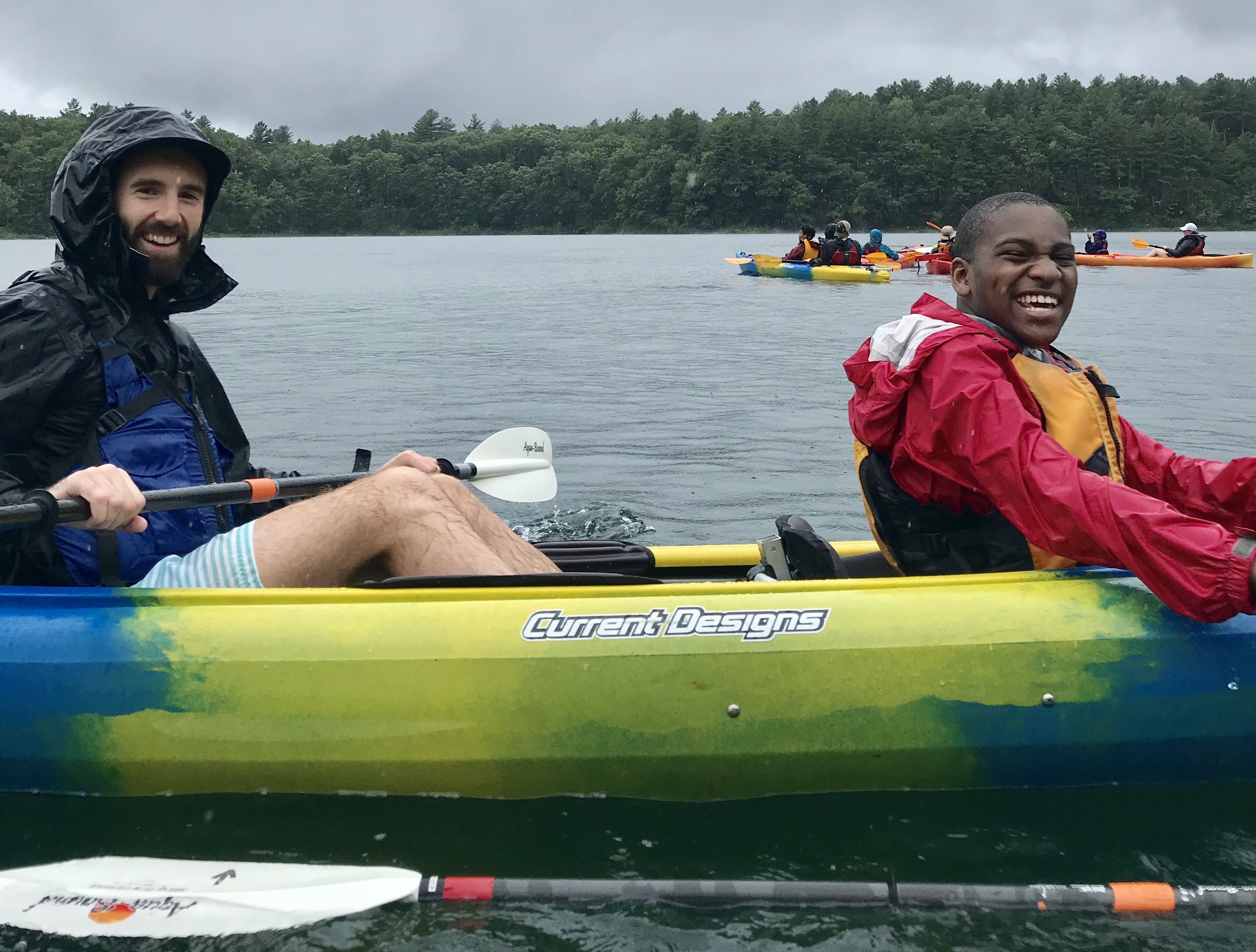 A volunteer and a participant paddling by smiling big with rain jackets on and it's raining