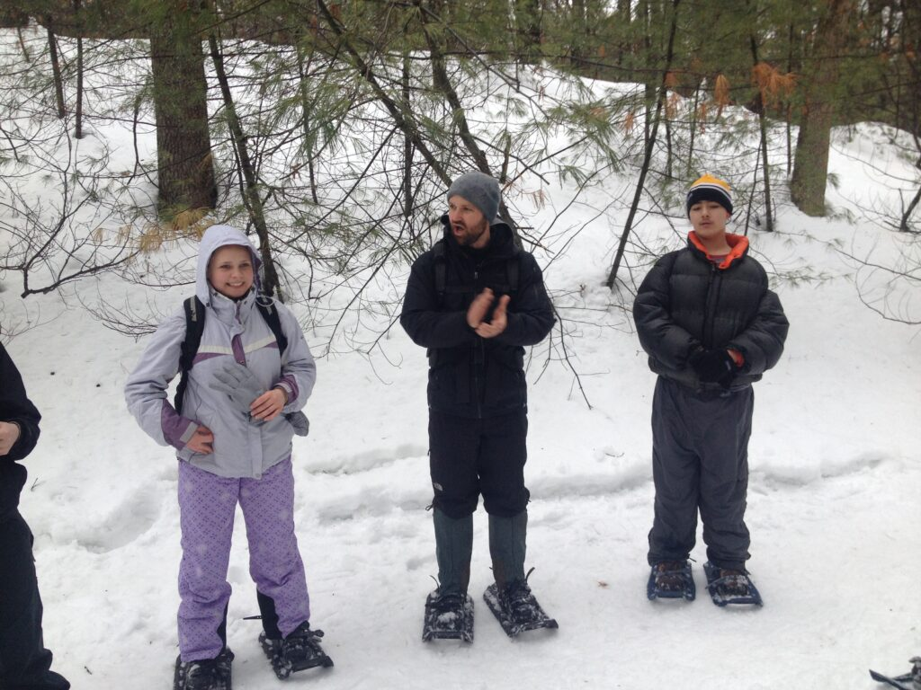 People standing with winter clothes getting ready to snowshoe