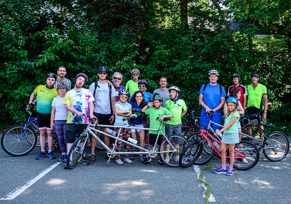 A group of people standing with bicycles smiling