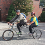 Two people on tandem bicycle riding on pavement