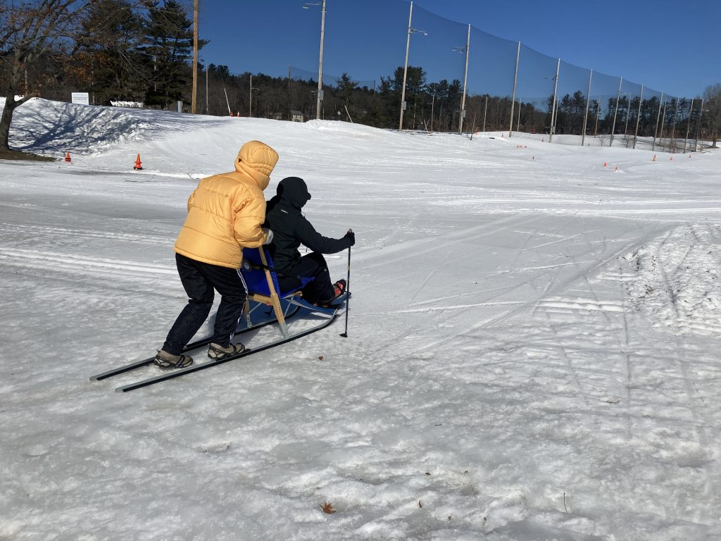 two people in snow gear, one on cross country skis pushing another using a sit ski
